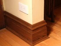 Установка в комнате широкого декоративного плинтуса из дерева