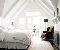 Дизайн белой спальни с камином на мансардном этаже