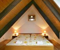 Дизайн небольшой спальни на мансарде под двускатной крышей
