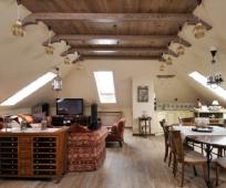 Интерьер жилой мансарды с гостиной и кухонной зоной