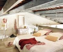 Потолочные балки и кирпичная отделка стен в мансардной спальне лофт