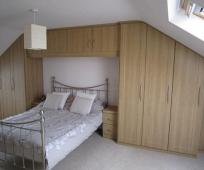 Встроенные мебельный гарнитур с навесным шкафчиком в спальне на мансарде