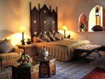 Кровать с высоким резным изголовьем в спальне марокканского стиля