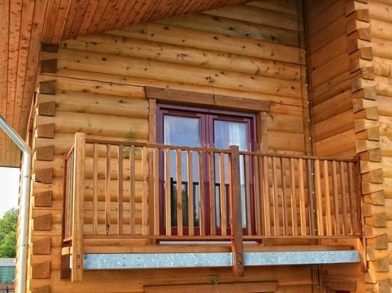 Балкон частного дома с деревянными перилами