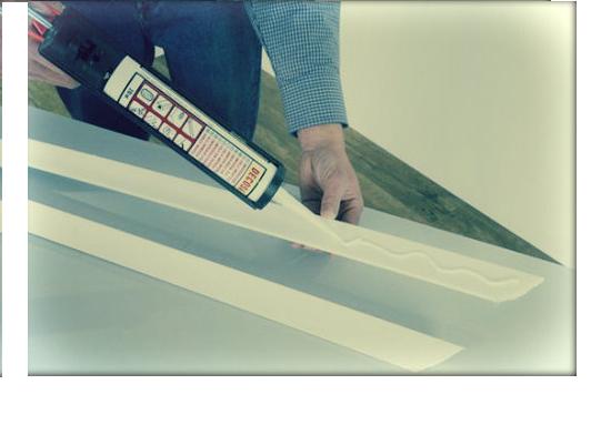 Нанесение клея на планку плинтуса для установки на потолок