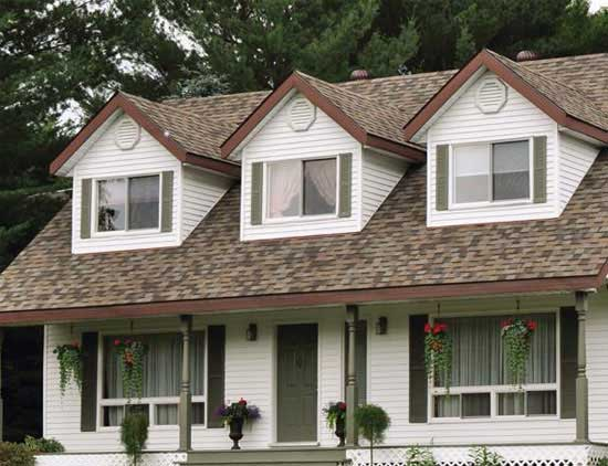 Слуховые мансардные окна в скате крыши дома