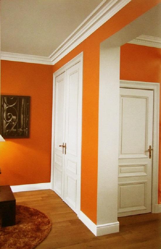 Белый широкий плинтус в комнате с белым потолком и ярко-оранжевыми стенами