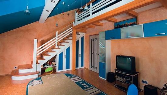 Интерьер просторной мансардной детской комнаты с лестницей на второй уровень