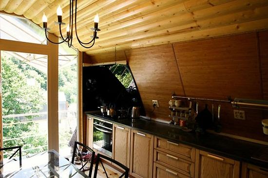 Дизайн кухни на мансардном этаже с рабочей зоной под скатом крыши