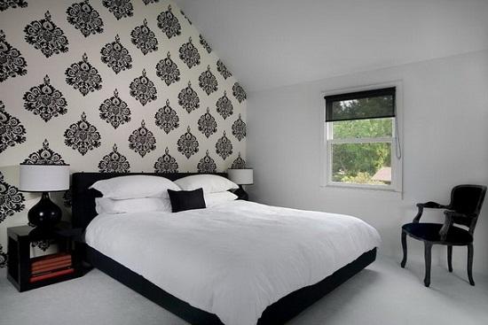 Дизайн светлой мансарды с оформлением стены у кровати контрастными обоями