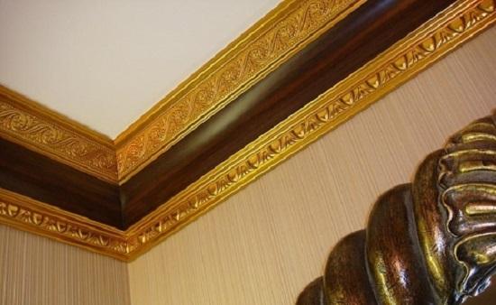 Плинтус с позолотой и сложным рельефом на потолке комнаты