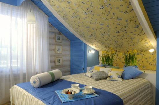 Уютная спальня на мансарде со встроенной мебелью под скатом крыши