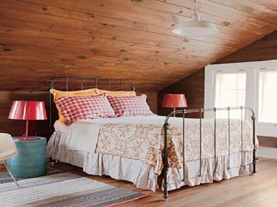 Дизайн мансардной спальни в стиле кантри с обшивкой деревом стен и потолка